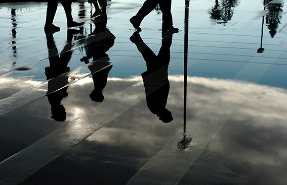 02/13/2006----KATHLEEN HINKEL---- People crossing the parking lot at Publix in Indian Harbour Beach are reflected in a puddle as the sun comes back out on Tuesday afternoon.  (Kathleen Hinkel/FLORIDA TODAY)